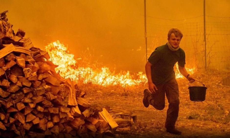 Fifteen year-old Alex Schenck carries a water bucket while fighting to save his home as the Ranch Fire tears down New Long Valley Rd near Clearlake Oaks, California, on Saturday, August 4, 2018. Noah Berger, AFP/Getty Images