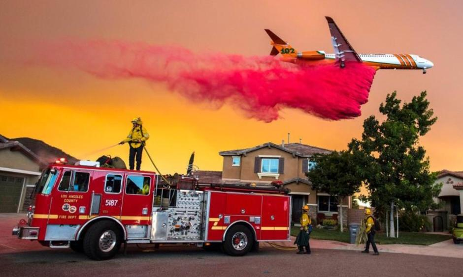 A plane drops fire retardant behind homes along McVicker Canyon Park Road in Lake Elsinore, California, as the Holy Fire burns near homes on Wednesday, Aug. 8, 2018. Photo: Weather Underground