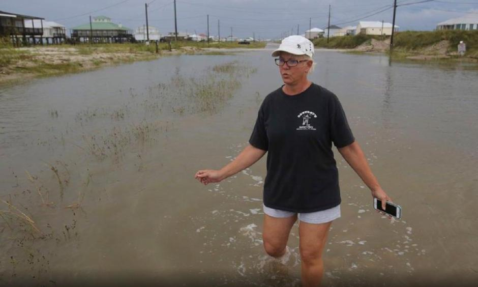 Susan Jones walks through a flooded road from Tropical Storm Gordon, Wednesday, Sept. 5, 2018, in Dauphin Island, Ala. Photo: Dan Anderson, AP