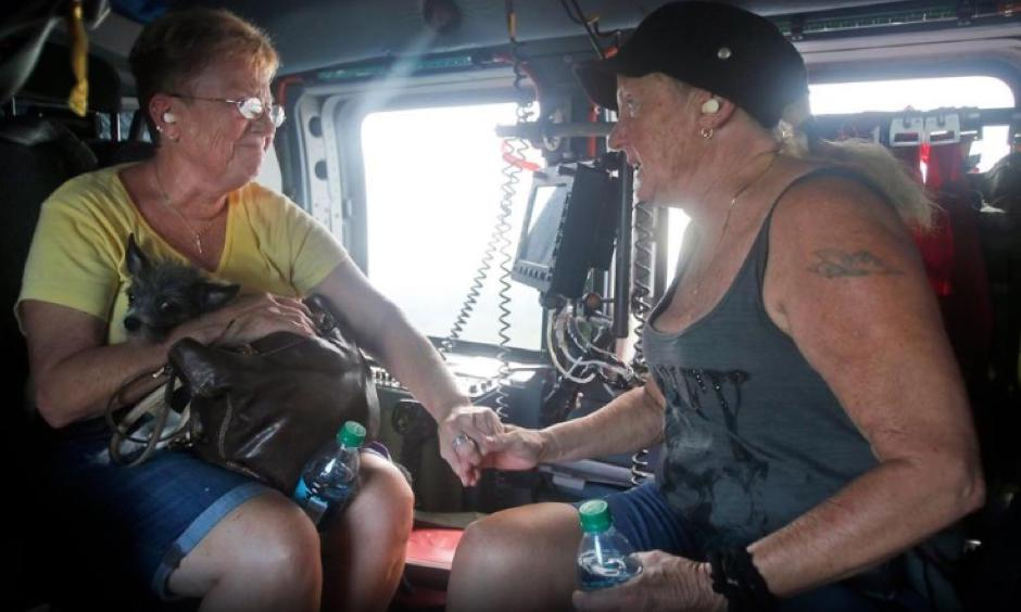 Wanda McGhee, left comforts Leann Davis in a Coast Guard helicopter after they were picked up from their flooded homes in Burgow, NC., Tuesday, Sept. 18, 2018. . Photo: Steve Helber, AP