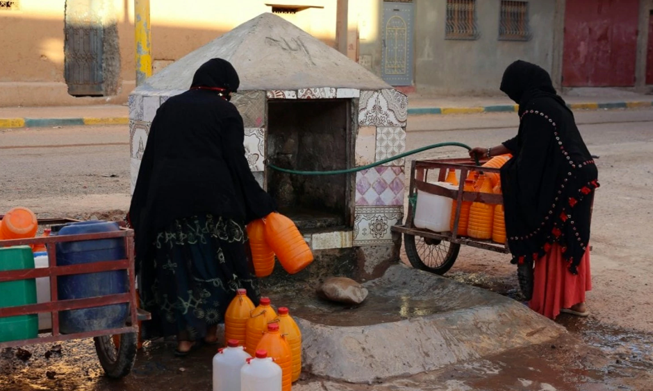 Women fill containers with water from a hose in Zagora, Morocco. Experts blame poor choices in agriculture, population growth and climate change for water shortages. Photo: Issam Oukhouya, Associated Press