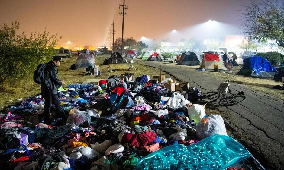 Evacuees sift through a pile of clothing at an encampment in a Walmart parking lot in Chico, California, on 17 November. Photo: Josh Edelson, AFP/Getty Images