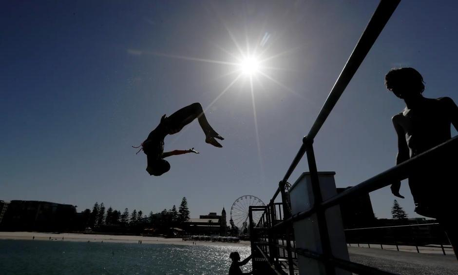 People in Adelaide head to the beach to escape Thursday's record-breaking Australia heatwave. Photo: Kelly Barnes, AAP