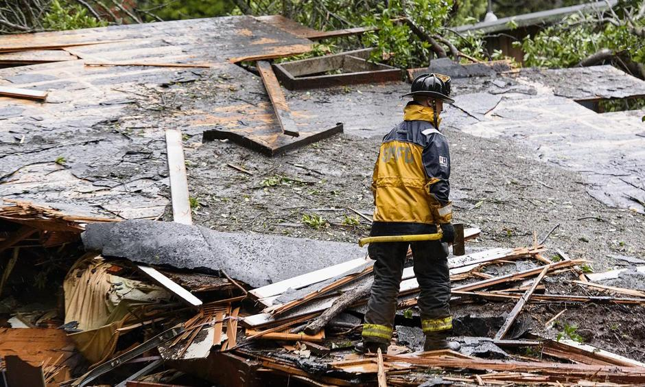 Southern Marin fire department members search a crushed house in the aftermath of a mudslide that destroyed three homes on a hillside in Sausalito, California, on Thursday. Photo: Michael Short, AP