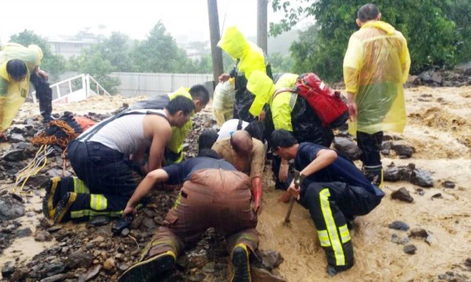 Firefighters dig out a family of seven that were caught in a landslide in New Taipei City's Wulai District yesterday during the onslaught of Typhoon Soudelor. All seven survived the ordeal. Photo: CNA