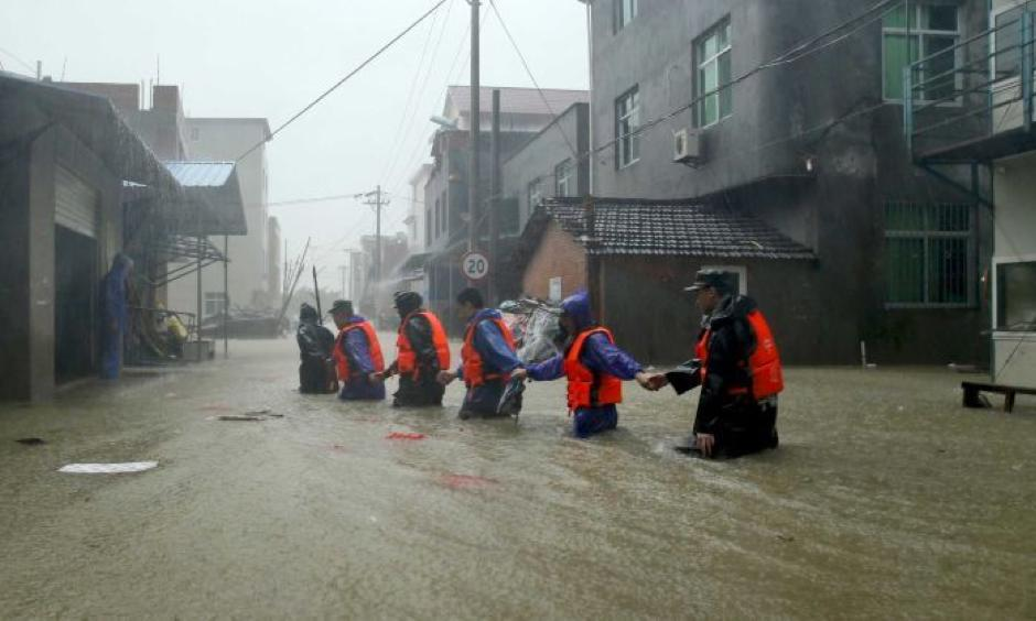 Rescue workers walk on a flooded street at a town hit by Typhoon Soudelor in China's Fujian province. Photo: Reuters, China Out