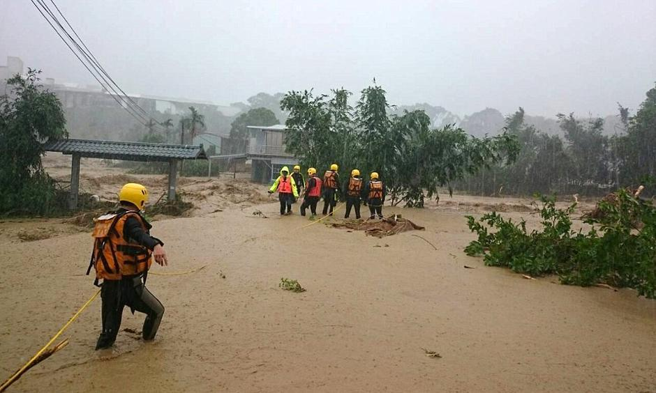 Rescue workers keep a wary eye on a mudslide in the aftermath of Typhoon Soudelor in Taiwan. The island's military put tens of thousands of troops and thousands of vehicles on stand-by for rescue operations. Photo: Xinhua, REX Shutterstock