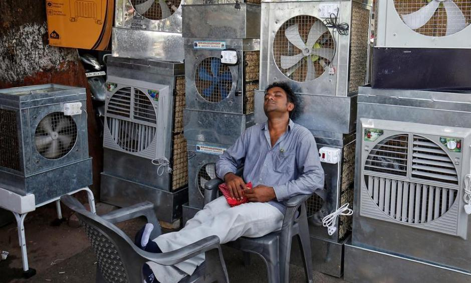 A man selling air coolers rests at a market on a hot summer day in Odisha. Photo: Reuters