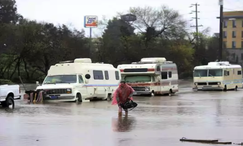 A man who lives in his RV in Salinas, Calif., walks through the flooded street on Mon., Feb. 20, 2016. Photo: Nic Coury, AP