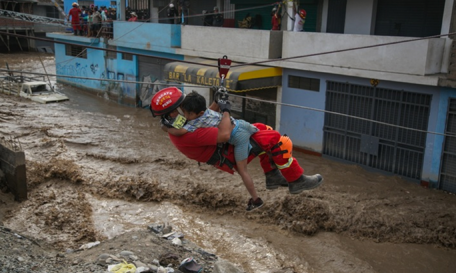 A policeman rescues a boy who was among people trapped in buildings by flash flooding in Lima, Peru. The El Niño climate phenomenon is causing muddy rivers to overflow along the Peruvian coast, isolating communities. Photo: AFP