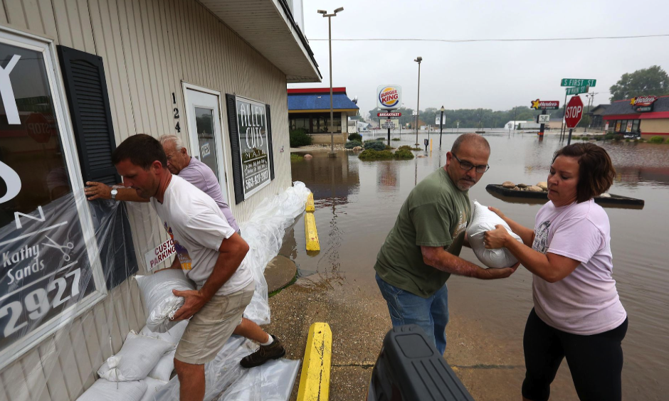 Holly Cole, right, and Michael Ridenou, second from right, work to build sandbag walls at the Alley Cuts on Main building along West Main Street Friday, Sept. 23, 2016, in Manchester. Photo: Jessica Reilly, Dubuque Telegraph-Herald AP