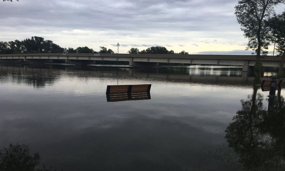 A park bench is rendered useless as the Cedar River continues its rise. Photo: Connor Morgan - KGAN