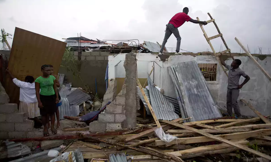 Residents repair their homes destroyed by Hurricane Matthew in Les Cayes. Photo: Dieu Nalio Chery/AP