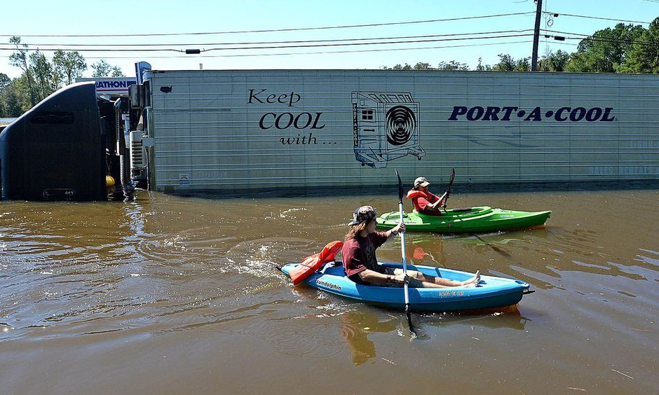 Anthony Writebol, left, and his cousin, Melissa Hill paddle past a stranded tractor trailer on Hwy 211 in Lumberton, N.C., Sunday, Oct. 9, 2016. Photo: Chuck Liddy, The Charlotte Observer via AP