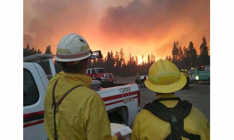 In this Sunday, Sept. 11, 2016 photo, firefighters observe a wildfire's push to the northeast, after initiating sprinkler systems to protect structures around Headwaters Lodge at Flagg Ranch in Moran, Wyo. Photo: National Park Service