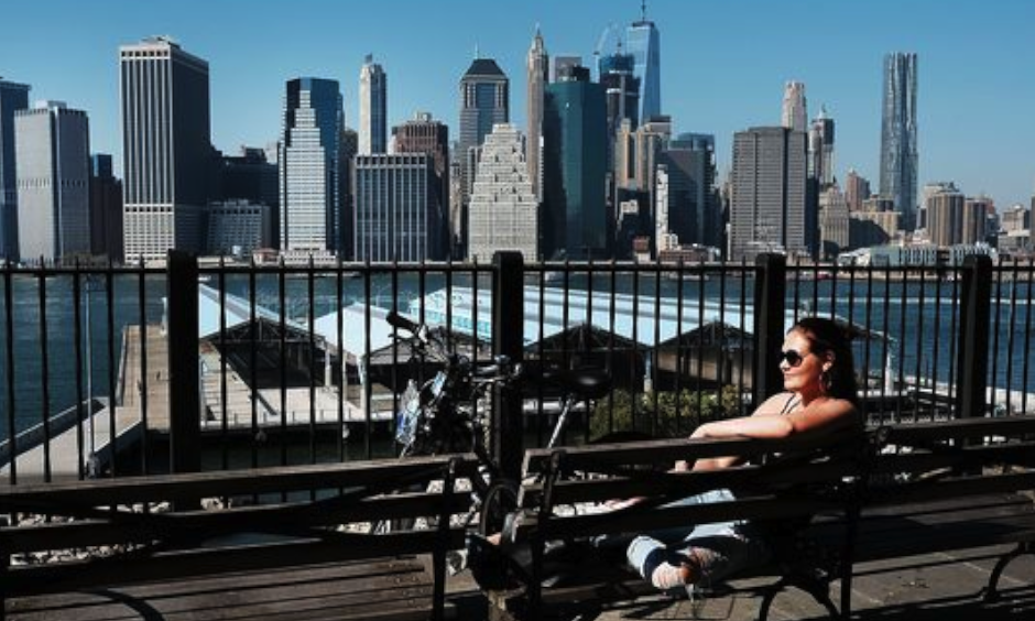 A woman sits in the sun on a summerlike day on Oct. 18, 2016, in the Brooklyn borough of New York City. New York and much of the East Coast are experiencing an Indian summer as temperatures reach into the high 70s. Photo: Spencer Platt, Getty Images