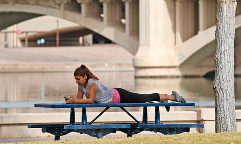 A woman relaxes next to Tempe Town Lake as temperatures are expected to break records again in Tempe, Ariz. Arizona is in the midst of a heat wave that has made October one of the hottest on records. Photo: Ross D. Franklin, AP