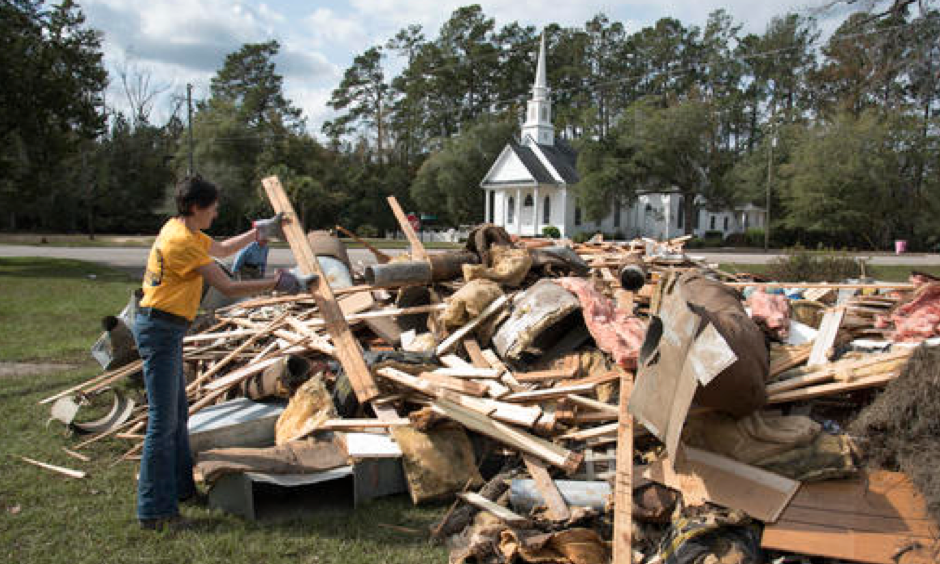 Wendy Gable, with Southern Baptist Convention Disaster Relief, throws wood onto a pile that was removed from a home that was heavily damaged by floodwaters caused by rain from Hurricane Matthew in Nichols, S.C., Thursday, Oct. 27, 2016. A stew of contaminants stood inches to feet deep in homes for a week. As it receded, toxic black mold grew rampant, leaving nearly all of the town's 261 homes uninhabitable. Few, if any, had flood insurance. Photo: Mike Spencer