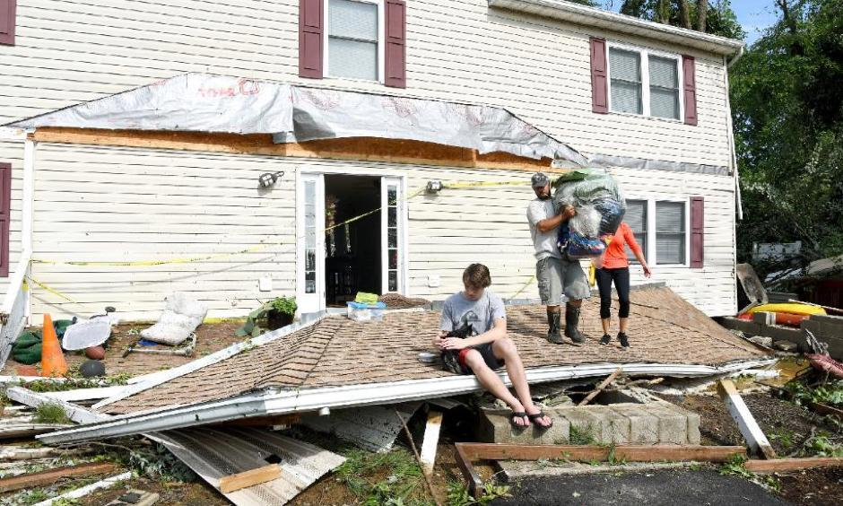 Brandon Testerman, 14, and his dog Tippy, sit on what was once part of his home's roof as other family remove belongings from the home in Bay City, Maryland, Monday, July 24, 2017. Photo: Paul W. Gillespie, The Baltimore Sun