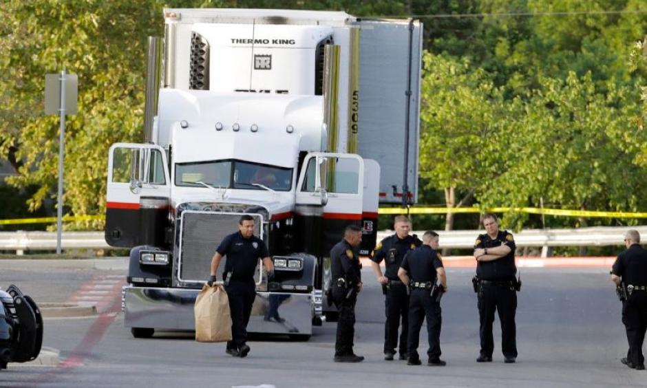 San Antonio police officers investigate the scene where eight people were found dead in a tractor-trailer loaded with at least 30 others outside a Walmart store. Photo: The Associated Press