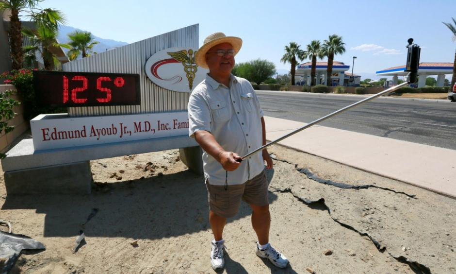 Palm Springs resident Benito Almojuela takes a selfie near a thermometer sign which reads 125 degrees in Palm Springs, California, June 20, 2016. Photo: Sam Mircovich / Reuters