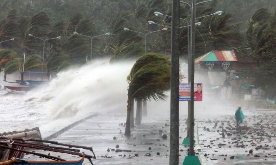 A resident walks past high waves pounding the seawall amid strong winds as Typhoon Haiyan hit the city of Legazpi, Albay province, Philippines, on Nov. 8, 2013. Photo: Charism Sayat, AFP, Getty Images