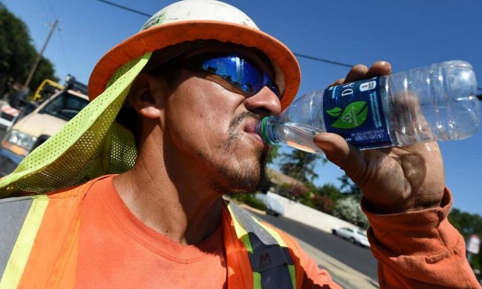 Miguel Lunar of Madco Electric takes a swig of cold water during work at Palm and Shields avenues to install traffic sensors under the roadway surface on June 21. Photo: John Walker, Fresno Bee