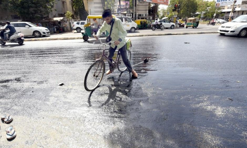 File photo: A cyclist in Ahmedabad struggles as tar melts on a road in summer last year. Photo: Yogesh Chawda, BCCL Ahmedabad