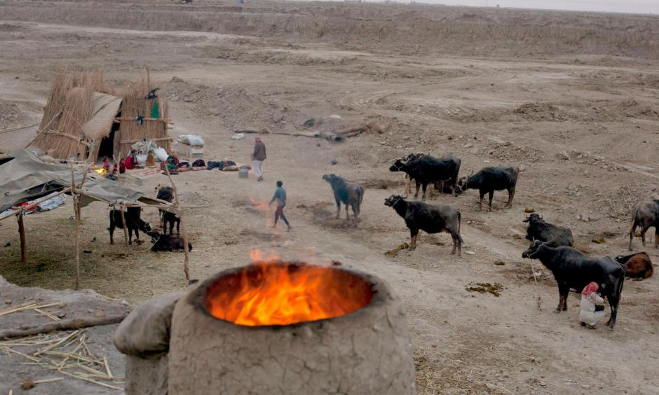 An oven burns near a family's reed hut in Chibaish, Iraq. The family moved to this area in search of water, but much of the former marshes remain desolate after years of draining and neglect. Photo: Carolyn Drake, Magnum