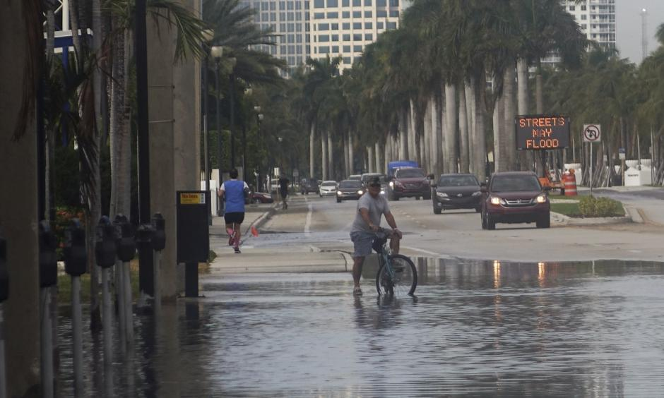 A bicyclist stops to negotiate Las Olas Boulevard, flooded by an unusually high tide known as a king tide, in Fort Lauderdale on Monday. Photo: Joe Cavaretta, South Florida Sun-Sentinel via Associated Press