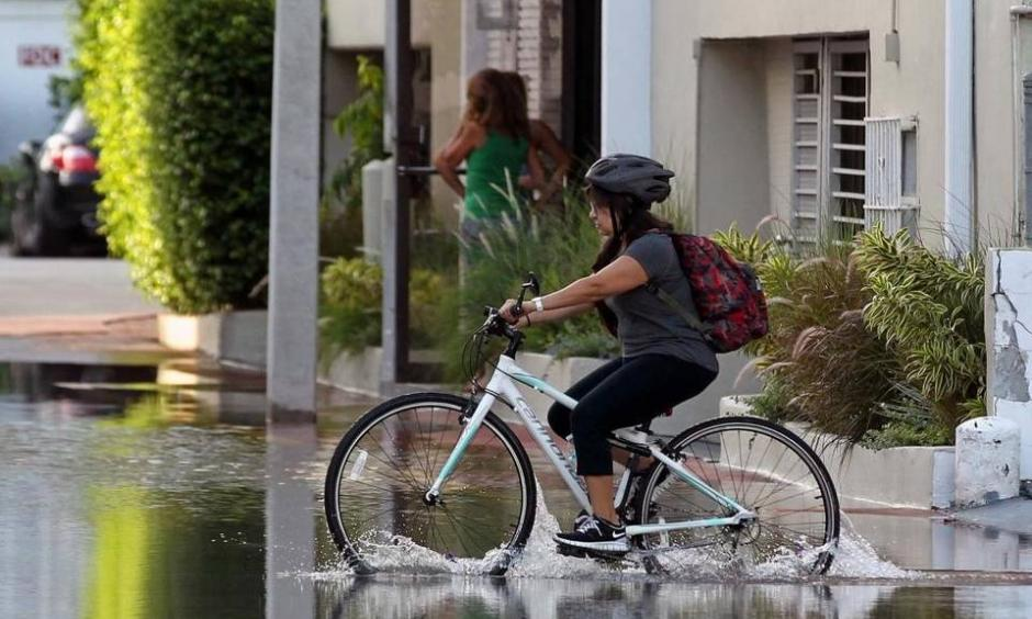 A young student on her bicycle carefully crosses the street on Lincoln Road Court in Miami Beach Thursday where the annual king tide caused flooding. Photo: C.M. Guerrero