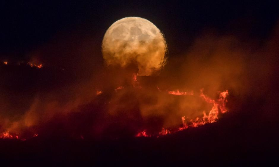 The full moon rises over the Saddleworth Moor fire. Photo: Getty