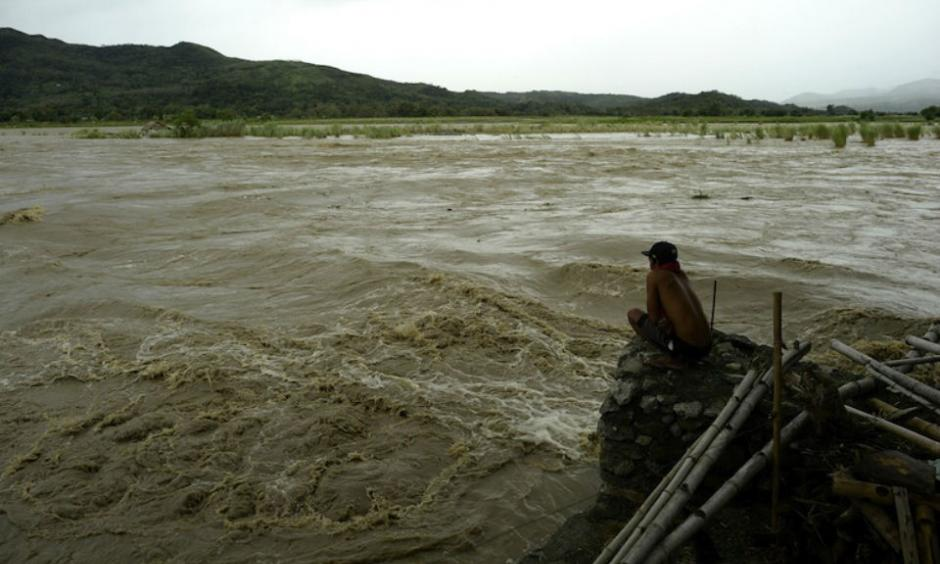 A man looks at the rising water level of the Magat River caused by continuous rains of Typhoon Koppu at Bayombong, Nueva Viscaya, Philippines, on Sunday, October 18, 2015. Koppu wrecked houses, tore down trees, and unleashed landslides and floods, forcing thousands to flee as it pummeled the northern Philippines on Sunday. Image credit: STR/AFP/Getty Images.