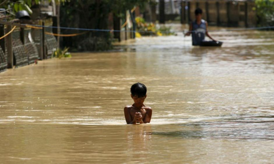 A boy wades through a flooded street in Jaen, Nueva Ecija, in northern Philippines: the death toll from Typhoon Koppu has now risen to 54. Photograph: Erik de Castro/Reuters