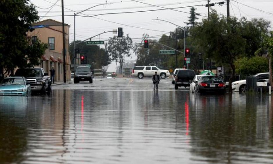 A man walks through floodwaters Monday in Salinas. Forecasters issued flash flood warnings throughout the Bay Area and elsewhere in Northern California. Photo: Nic Coury / Monterey County Weekly