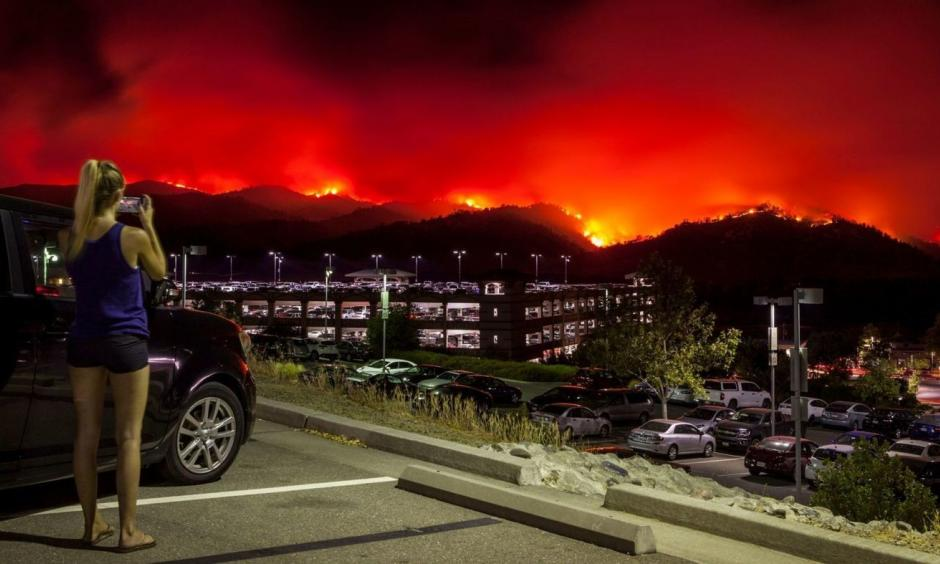 A woman takes photos from the upper parking lot of the Cache Creek Casino Resort overlooking the County fire as it burns out of control Saturday in Brooks, Calif. The blaze spread quickly overnight. Credit: Peter DaSilva, EPA, Shutterstock