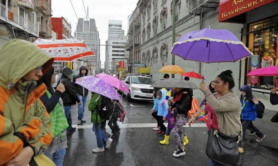 Pedestrians take cover in the Chinatown district of San Francisco as a powerful storm rolled into the Bay Area. Image: Ben Margot / Associated Press)