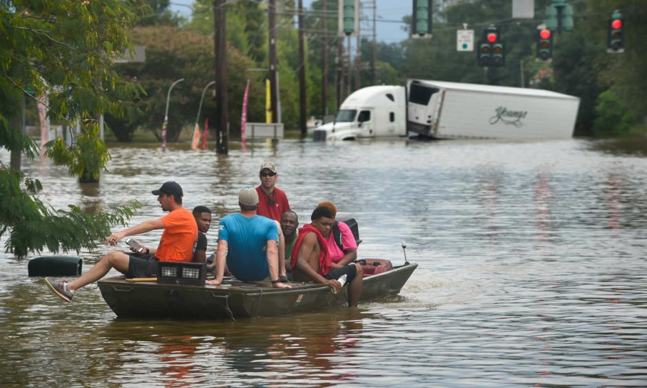 A small boat transports flood victims down Old Hammond Highway in east Baton Rouge on Aug. 14, 2016. Photo: Travis Spradling, The Advocate