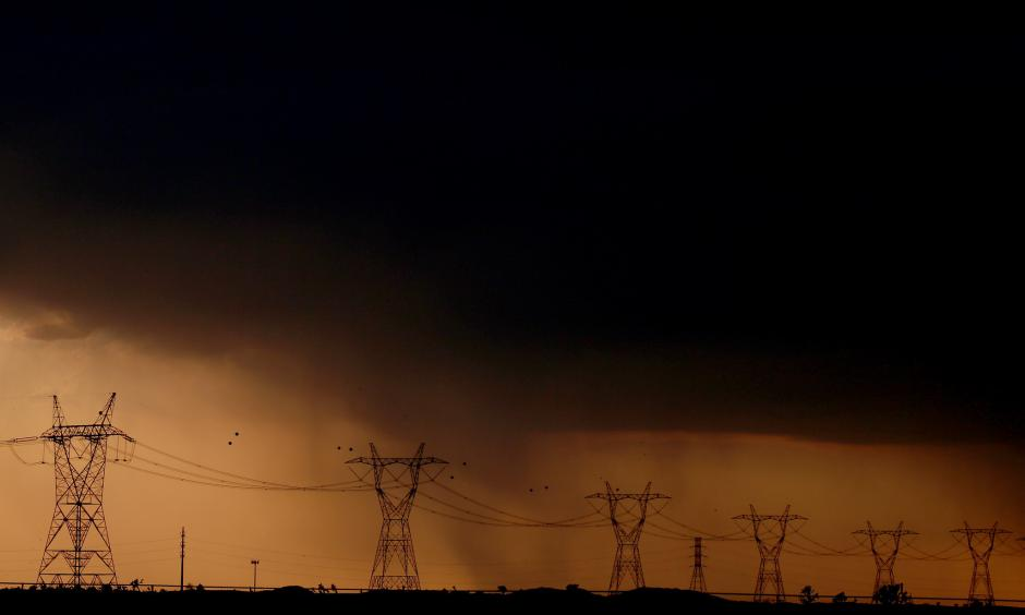 Rain falls behind power lines near Adelanto at the end of a scorching hot day. Photo: Luis Sinco / Los Angeles Times
