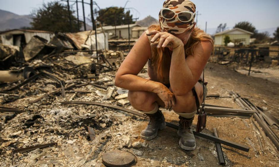 Tyra Rene Fuller tears up a she finds a porcelain cast of her daughter's handprint while soring through what's left of her belongings after her home was destroyed by the Erskine fire in Lake Isabella, Calif. Photo: Marcus Yam / Los Angeles Times