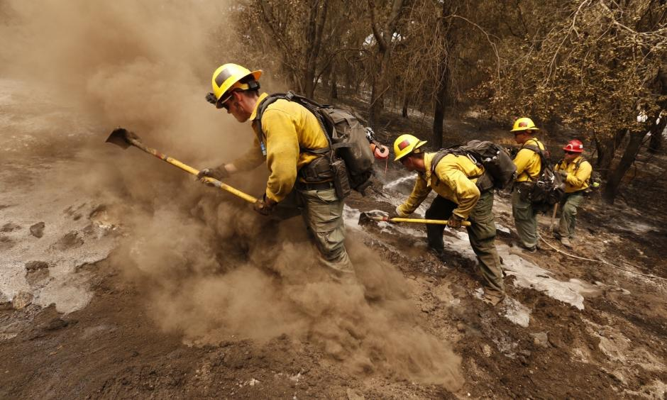 From left, firefighters Aaron Williams, Lyle Bennett, Robert Larios and Capt. Crawford Gunn, with the San Bernardino National Forest, put out hot spots Monday morning along Highway 154 in Santa Barbara County. Photo: Al Seib, Los Angeles Times