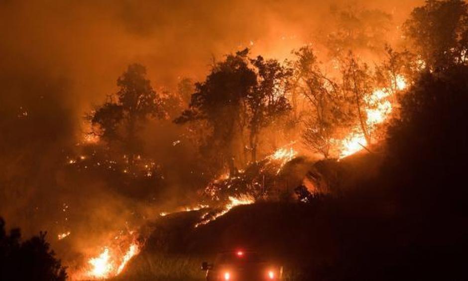Flames from the Detwiller fire spread down a hillside near Mariposa, California on July 17, 2017. Photo: Noah Berger, EPA