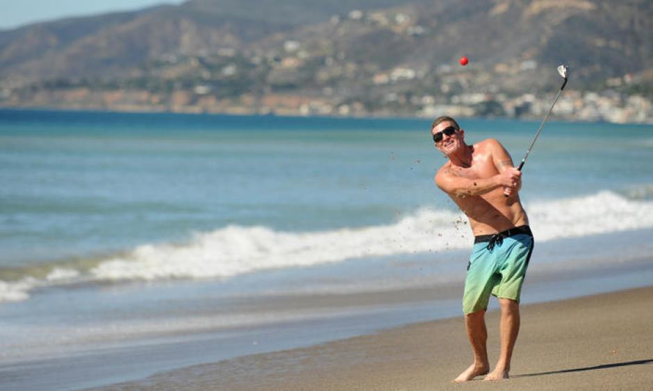 Dan Charcoal, who is vacationing in Southern California from Maui, golfs on Zuma Beach during a hot winter day Monday. Photo: Wally Skalij, Los Angeles Times