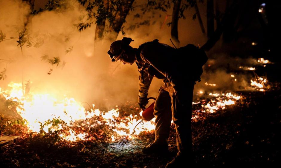 Brandon Tolp, a San Bernardino-based firefighter, performs a firing operation to prevent the flames from crossing Highway 29 on Oct. 12. Photo: Marcus Yam / Los Angeles Times