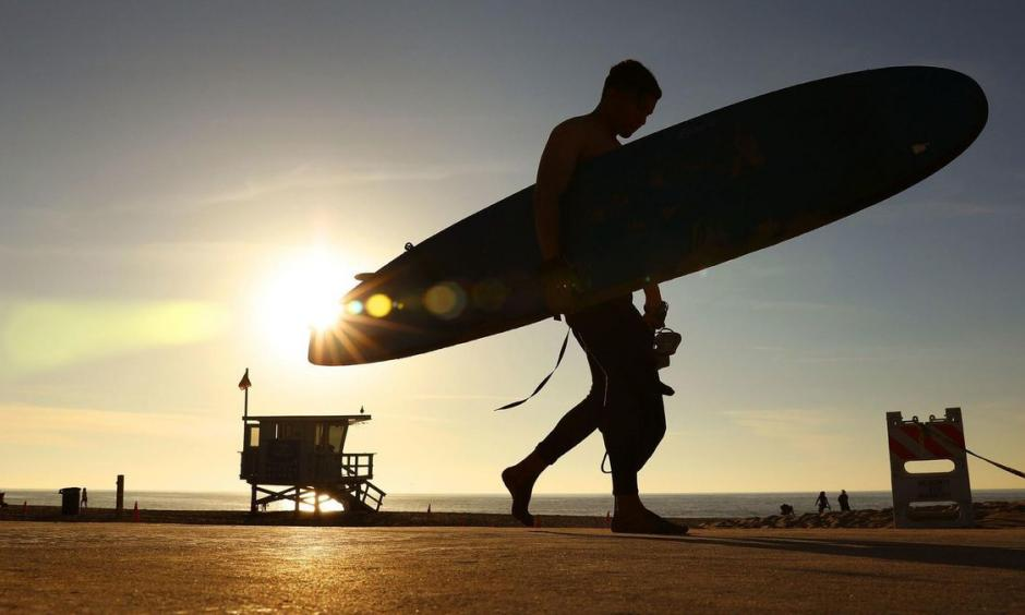 A surfer in Redondo Beach walks past the setting sun on Sunday. Photo: Christina House, Los Angeles Times
