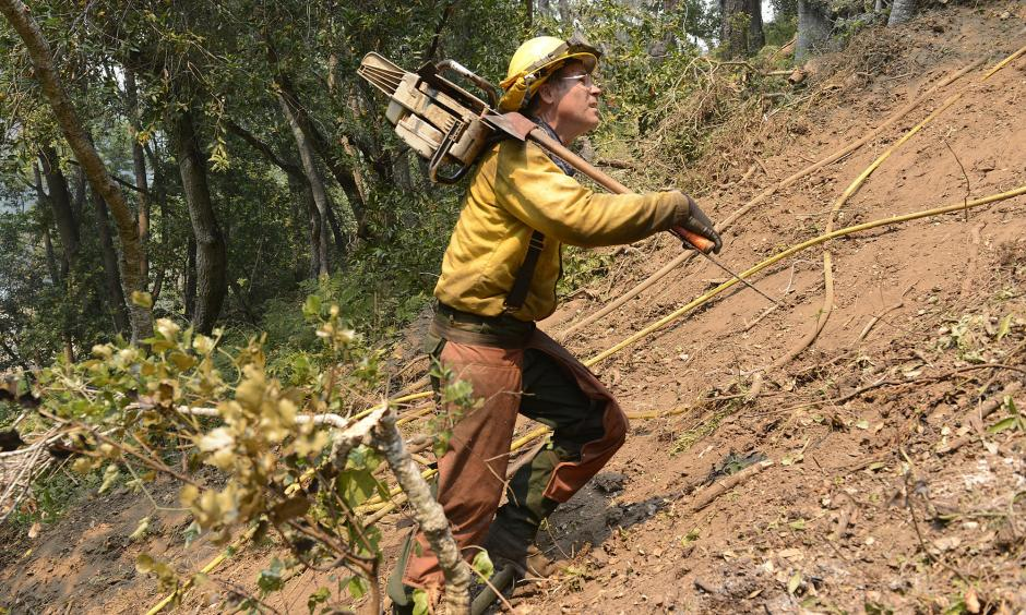 Jeff Turpin hikes up a hillside with his chain saw Saturday while cutting a fire break for the Soberanes fire. Photo: David Royal / Monterey County Herald via AP