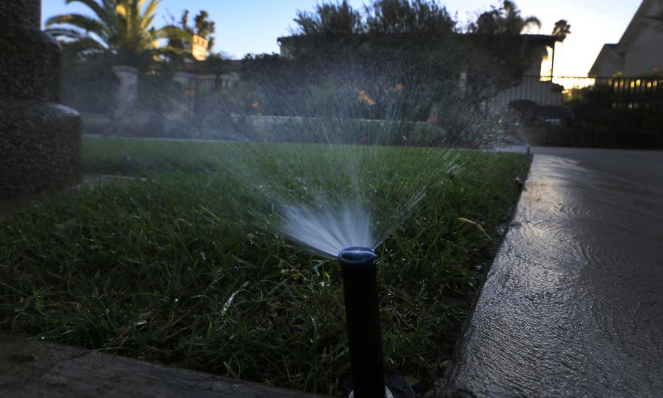 Sprinklers water a lawn at dusk in Beverly Hills. Statewide, Californians cut their urban water use in March by 24.3% compared with the same month in 2013, regulators said. Photo: LA Times