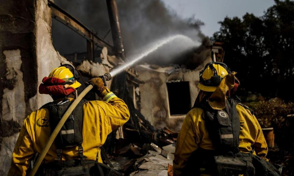 Humboldt County firefighters Bobby Gray, left, hoses down smoldering flames inside a destroyed home Marcus Yam, Los Angeles Times