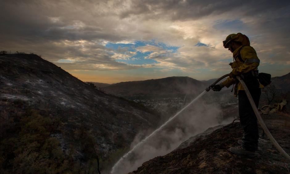 Los Angeles County firefighter Kevin Sleight extinguishes hot spots while battling the La Tuna fire. Photo: Allen J. Schaben / Los Angeles Times
