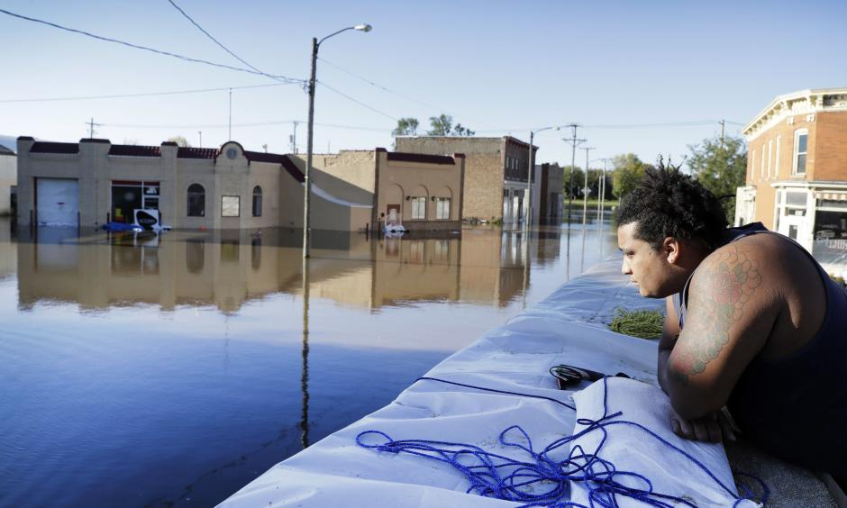 Cory Harrison stands on a flood wall as he looks over businesses flooded by the Cedar River on Sept. 27 in Cedar Rapids, Iowa. Photo: Charlie Neibergall, Associated Press)